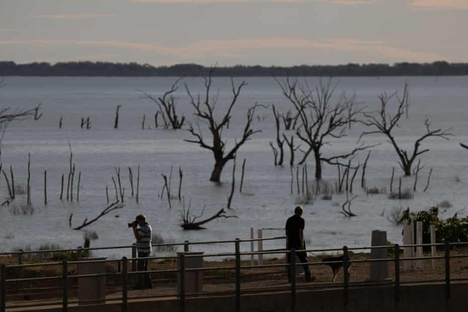 Tourists on the weir as the sunsets over Menindee Lake.