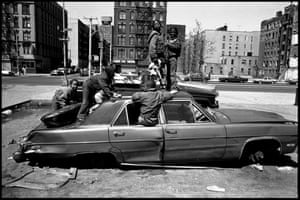 Youths play in a car in Harlem in New York in 1987