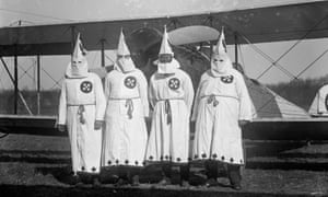 Four Hooded White Sheeted Ku Klux Klan Members pose in front of an airplane c1922.