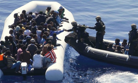 German navy sailors reach a migrants' boat off the coast of Libya in March 2016.