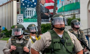 LA sheriff's deputies stand guard as activists and relatives of Andres Guardado hold a rally near the Compton station.