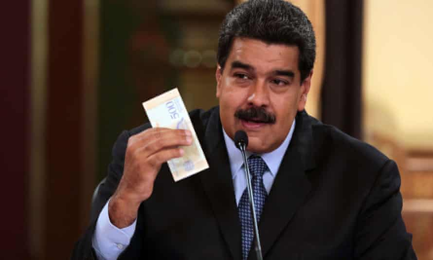 Maduro holds up a rebranded bolivar in a television broadcast from the presidential palace.