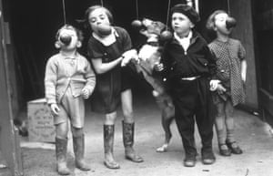 Children and their dog play a hands-free egg-eating game, Cardiff, 1937.