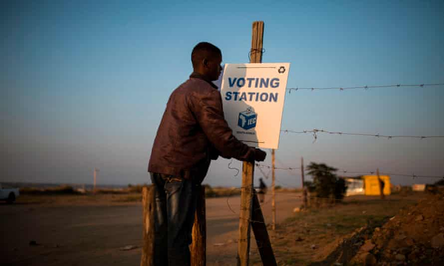 A resident hanging a 'voting station' sign near the South African city of Polokwane