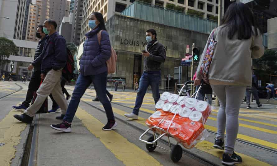 A woman carries a trolley of toilet rolls along a street in hong kong
