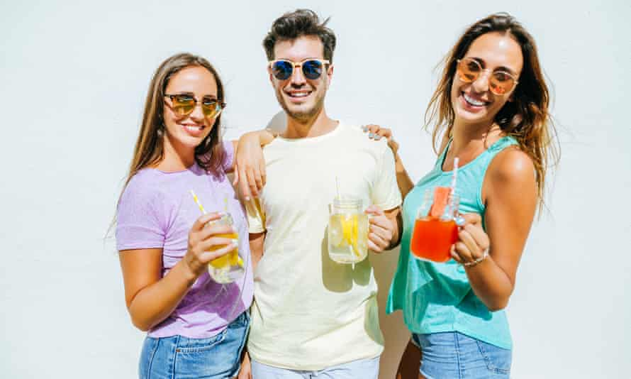 A man and two woman holding lemonades and looking happy