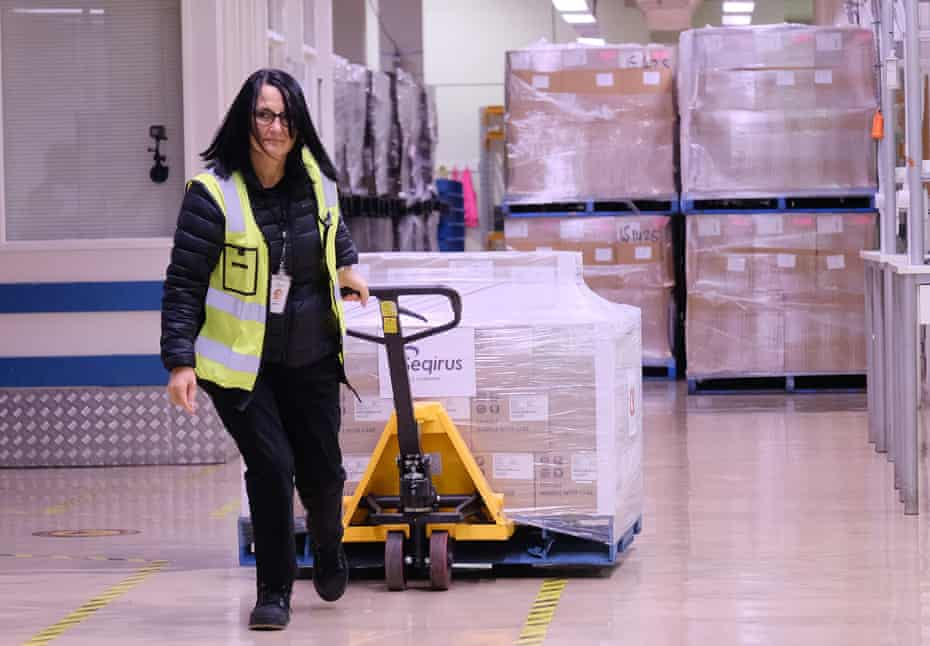 A worker prepares to load a truck with the first batch of the AstraZeneca Covid vaccine produced in Australia