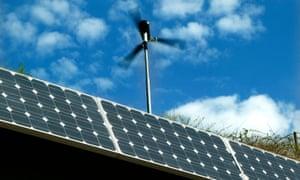 A wind turbine above an array of solar cells