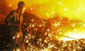 A worker pries up molten cast iron from a blast furnace at a plant in Liaoning province of China.