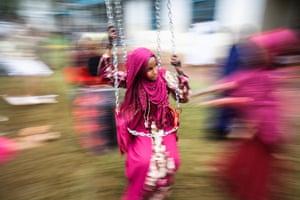 A young Muslim girl enjoys a swing ride at Eastleigh High School in Nairobi, Kenya