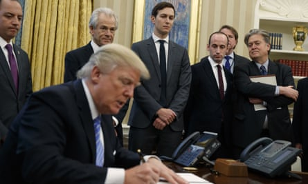 Reince Priebus, Peter Navarro, Jared Kushner,  Stephen Miller and Steve Bannon watch as Donald Trump signs an executive order in the Oval Office, 23 January 2017