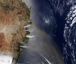 A from Nasa Earth Observatory shows a satellite image of the bushfires raging near the coast of New South Wales, sending smoke billowing over the Tasman Sea