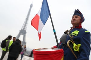 A man wearing a uniform and holding a French flag stands in front of the Eiffel Tower in Paris on March 23, 2019, during an anti-government demonstration called by the 'Yellow Vest' (gilets jaunes) movement in Paris.