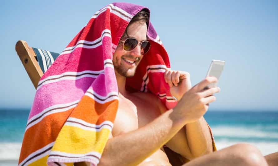Man looking at his smartphone on a sunny beach