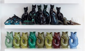 Two shelves, one with a row of 9 ceramic fish, the other with tall sitting black cats