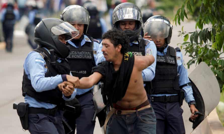 Policemen detain a demonstrator during a march against the government's plans to privatize healthcare and education, in Tegucigalpa, Honduras, on Tuesday.