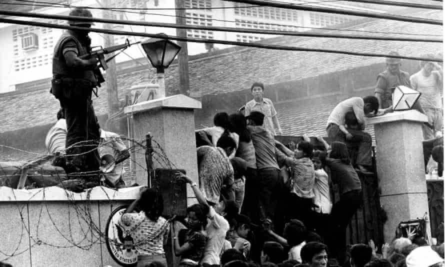Mobs scale the wall of the US embassy in Saigon, just before the end of the Vietnam War in 1975.