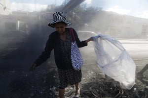 A woman searches the debris of a barricade erected by protesters for plastic bottles to recycle in Tegucigalpa, Honduras