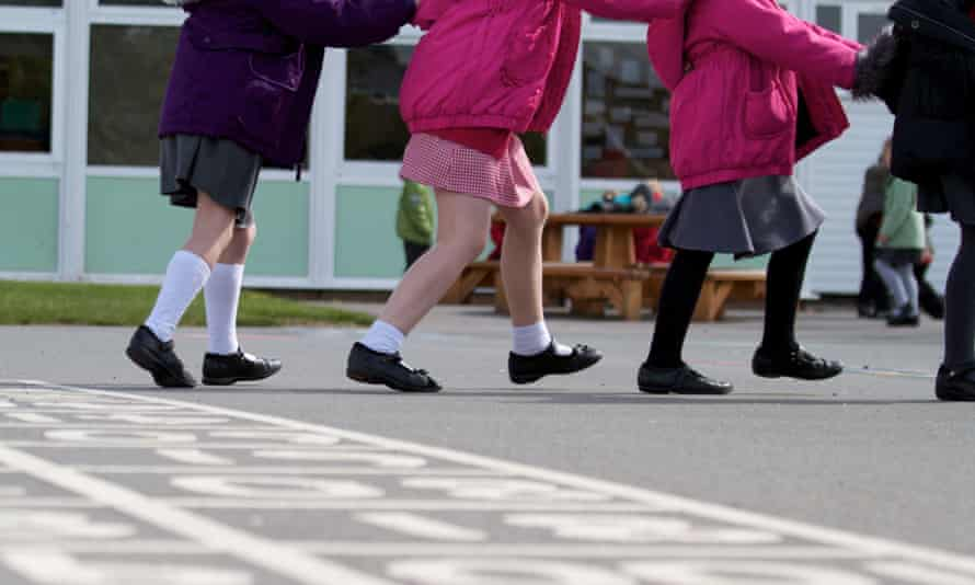 A line of schoolchildren play on a school playground