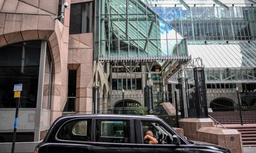 A taxi driver is seen sleeping in his cab outside a quiet office building in the City of London.