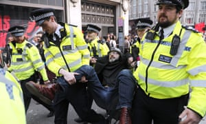 Police carry a male protester by his arms and legs
