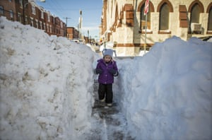 Beatrice Evangeline, 3, walks through a narrow shovelled path in Philadelphia