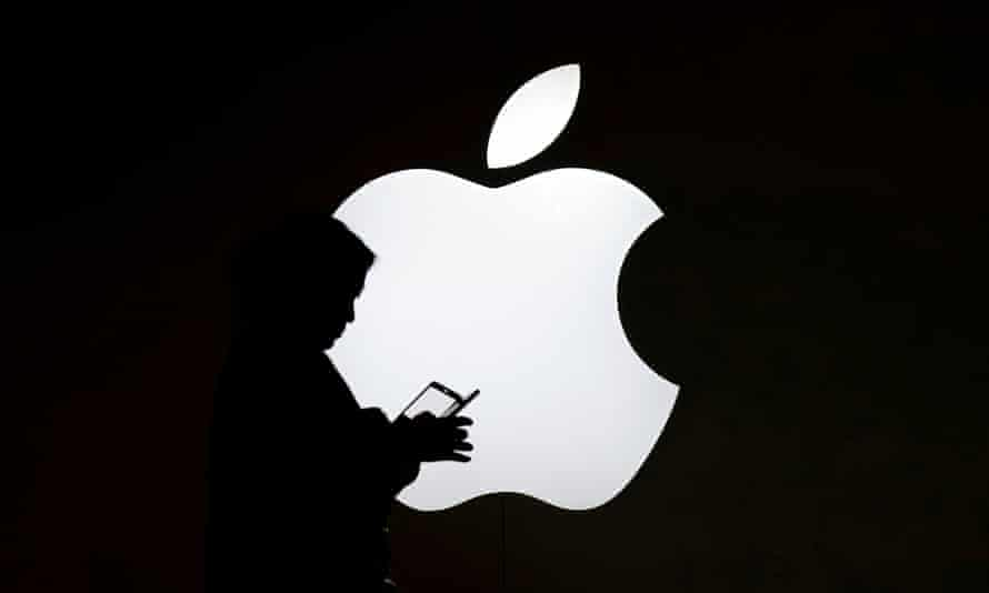 A woman uses a phone in front of an iphone logo