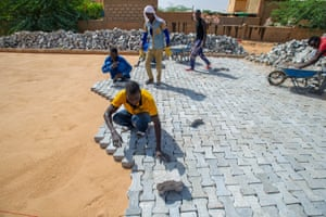 Men pave a road with bricks as part of an EU-funded job scheme in Agadez, Niger