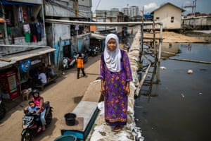 Sukaesih stands on top of a sea wall in the Muara Baru district where she lives. When tides are high, the water pours over.