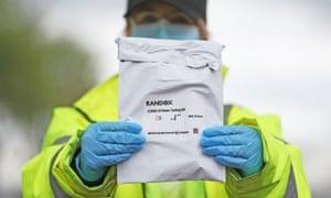 A testing worker holds a Randox test kit