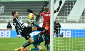 Newcastle's Fabian Schar clears the ball off the line under pressure from Liverpool's Sadio Mane.