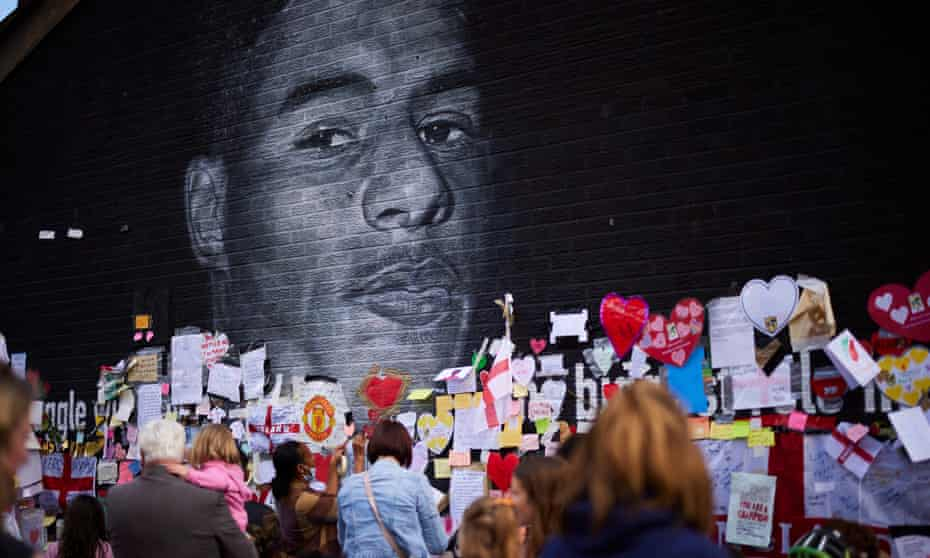 Crowds gather at a mural of Marcus Rashford in Withington. The portrait had been defaced with racist graffiti after the Euro 2020 final.