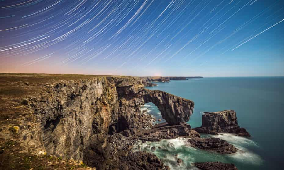 Star trails spiral above the Green Bridge of Wales, illuminated by a near full moon on the south Pembrokeshire coastline