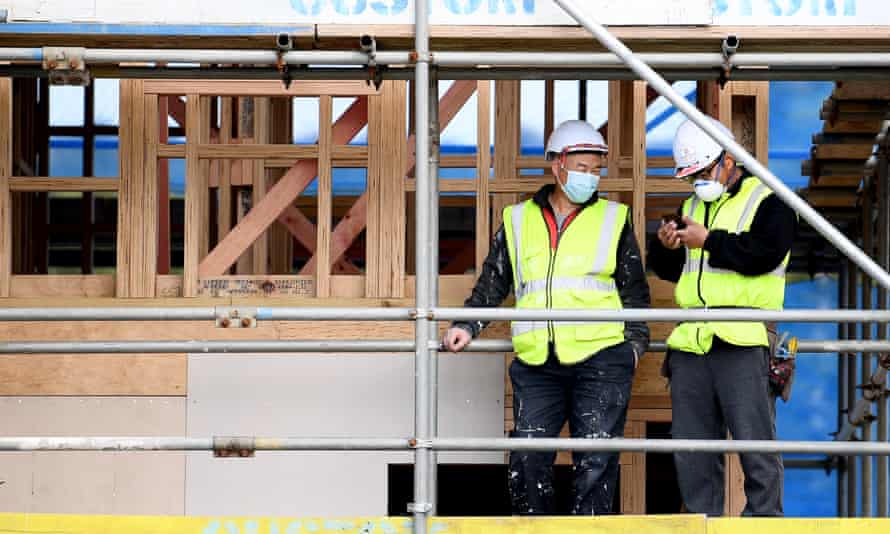 Two workers in hi-vis and hard hats on a public housing development in Auckland
