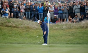 Tommy Fleetwood chips onto the green as spectators line up at the sixth.