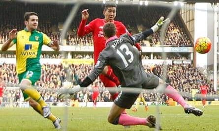 Roberto Firmino flicks the ball past the Norwich goalkeeper Declan Rudd for Liverpool's third goal.