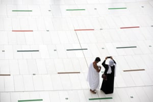 A couple take photos of the Kaaba before the Hajj pilgrimage takes places under special socially-distanced conditions.