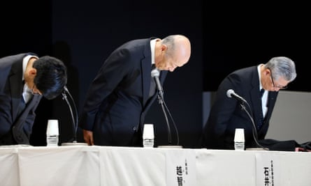 Dentsu president Tadashi Ishii, centre, bows during press conference where he announced his resignation.