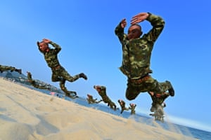 <strong>Shenzhen, Guangdong Province, China</strong> Frontier soldiers take part in an exercise on a beach. Heat wave sustained in Guangdong, where ground temperature got close to 60 Celsius degress by the sea