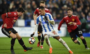 Victor Lindelöf (left) takes the ball from Huddersfield's Tom Ince.