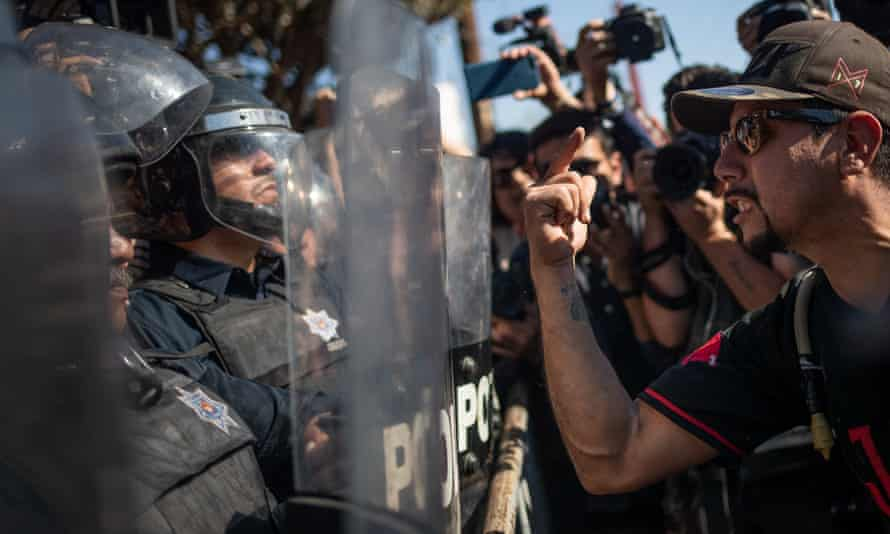 A demonstrator shouts at the riot police guarding a shelter housing a caravan from Central America in Tijuana