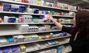 Pharmacy worker takes drugs from shelves.