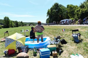 Spectators refresh themselves in a swimming pool as they watch cyclists riding past on the fourth stage between Reims and Nancy.