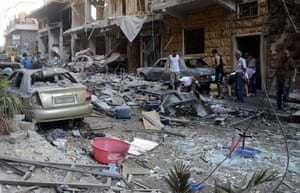 Syrians stand amid the damage in a street in the ancient Syriac quarter of Aleppo following rocket attacks by rebels