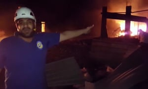 In this grab taken from video provided by the Syrian Civil Defence White Helmets, a member of the team describes the damage after an airstrike, in Aleppo, Syria.