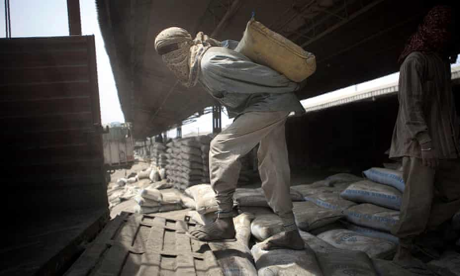 Laborers load cement bags manually onto transport carriers at the Shakur Basti station in New Delhi, India.