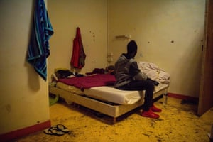 A young migrant sits on a bed in the foyer Saint Just shelter in Marseille.