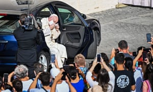 Pope Francis takes off his face mask as he arrives by car to hold a limited public audience at the San Damaso courtyard in The Vatican on 9 September 2020.
