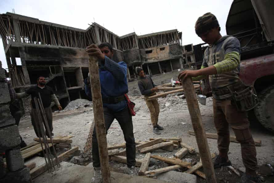 Iraqi workers repair a building on March 15, 2018 eight months after Iraqi forces liberated the city from the control of the Islamic State (IS) group fighters.