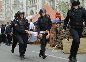 A protester is carried by police officers away from a rally in central Moscow